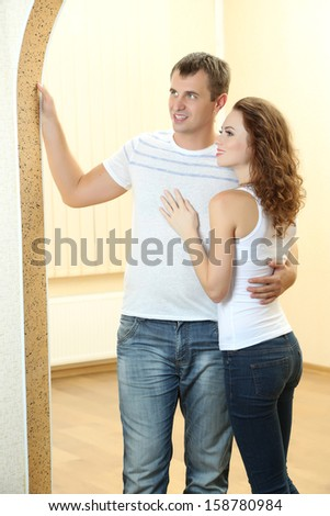 Young couple in new house on room background - stock photo