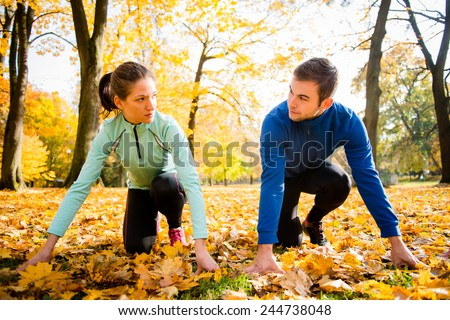 Young couple in ready position prepared for running in autumn nature - stock photo