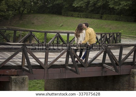 Young couple in 20s, leaning on wooden bridge. In nature, park. surrounded with beautiful nature landscape.