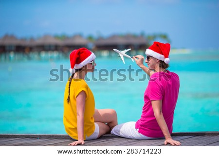 Young couple in Santa hats relaxing on wooden jetty on Christmas vacation