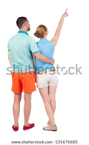 young couple in shorts and t-shirt pointing. Back view.  Rear view people collection.  backside view of person.  Isolated over white background.