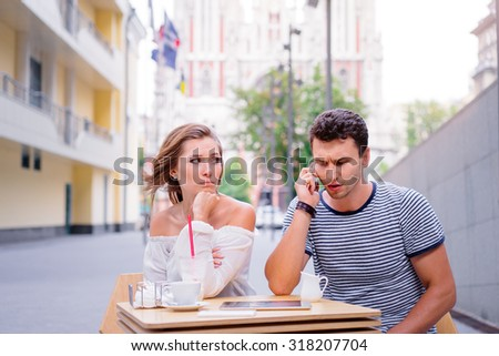 Young couple in sidewalk cafe. Attractive woman is angy with her boyfriend, who talking by phone. - stock photo