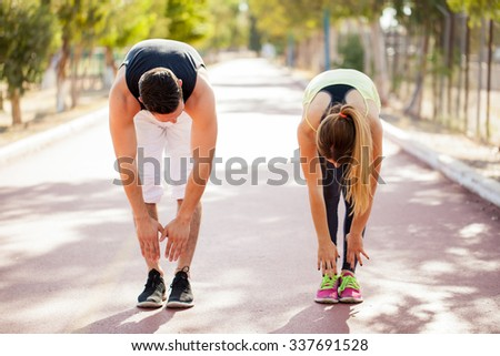 Young couple in sporty outfit doing some stretching outdoors before jogging together - stock photo