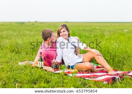 Young couple in summer meadow, man and woman having romantic picnic