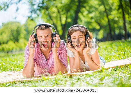 Young couple in summer park listening music