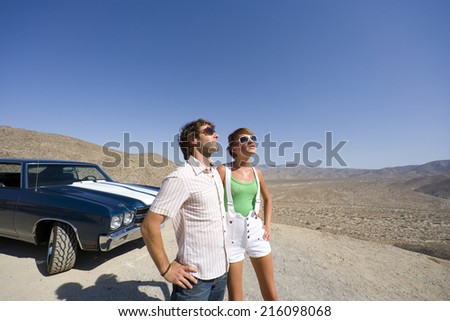 Young couple in sunglasses by car in desert, looking up