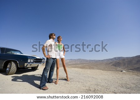 Young couple in sunglasses by car in desert, low angle view