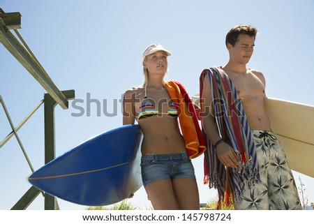 Young couple in swimwear carrying surfboards at beach - stock photo