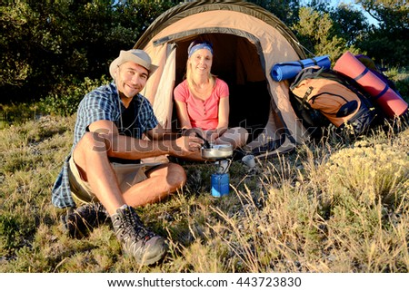 young couple in tent camp on summer outdoor adventure hiking trip