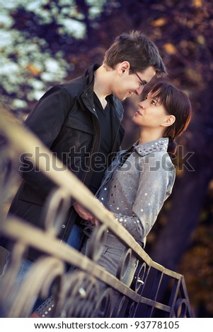 Young couple in the autumn park, looking in each others eyes - stock photo