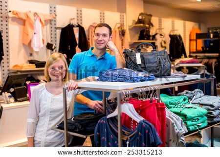 young couple in the clothes shop looking in to the camera