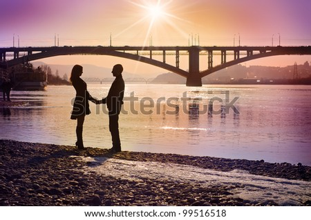 Young couple in the evening under the bridge - stock photo