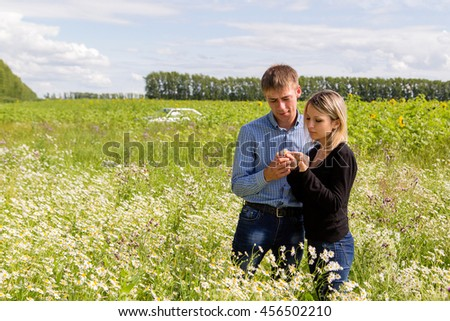 young couple in the field. Looking at flower.