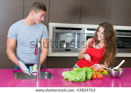 young couple in the kitchen washing cups and doing salad