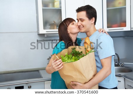 Young couple in the kitchen with a bag of groceries shopping - stock photo