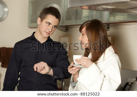 Young couple in the morning drinking coffee in the kitchen