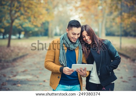 young couple in the park during autumn season outdoor - using tablet technological device  - stock photo