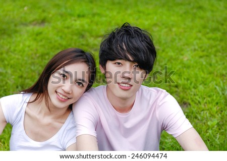 Young couple in the park sitting on the grass - stock photo