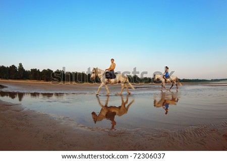 Young couple in the sea on horseback - stock photo