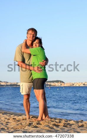 Young couple in the sunset light on the beach - stock photo