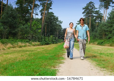 Young couple in their twenties holding hands and walking on the grass in a forest landscape late summer