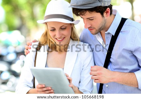 Young couple in town using electronic tablet - stock photo