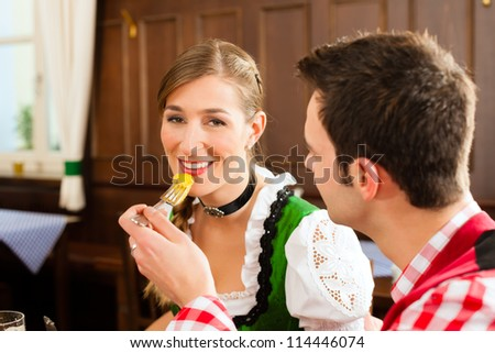 Young couple in traditional Bavarian Tracht eating in restaurant or pub lunch or dinner - stock photo