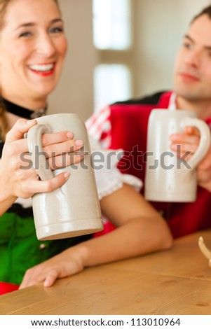 Young couple in traditional Bavarian Tracht in restaurant or pub with beer - stock photo