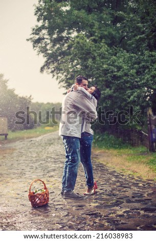 Young couple in Ukrainian style clothes kissing while standing under rain