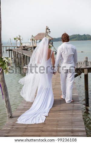 young couple in wedding dress walking along the pier - stock photo