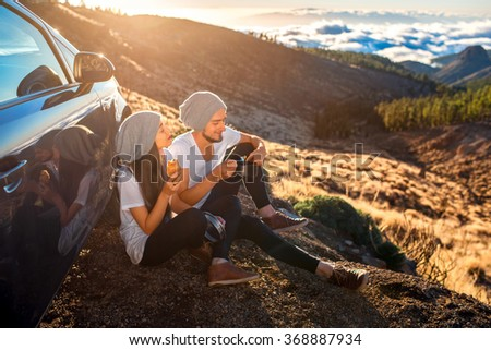 Young couple in white t-shirts and hats having picnic with croissant and cooking pan near the car on the mountain roadside above the clouds - stock photo