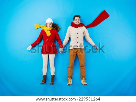 Young couple in winter clothes on blue background - stock photo