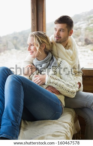 Young couple in winter clothing looking out through cabin window - stock photo