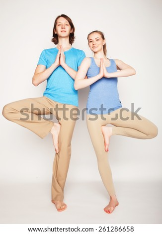 Young couple in yoga pose, happy family - stock photo