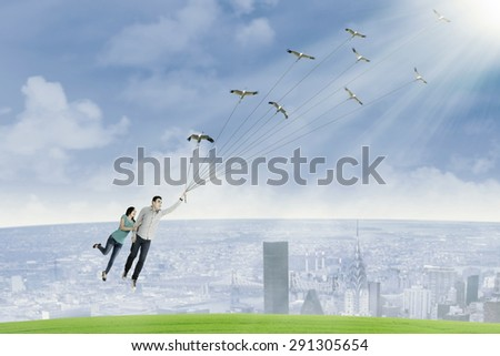 Young couple is flying by holding birds over a green meadow - stock photo