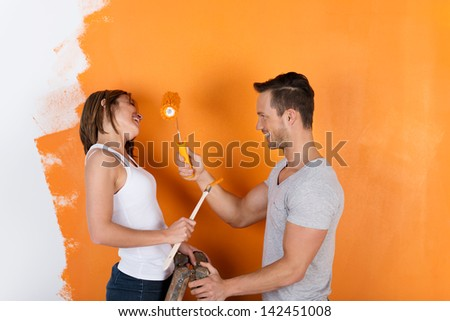 Young couple is having fun redecorating and painting - stock photo
