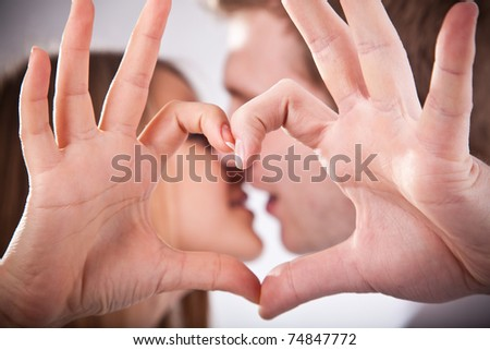 Young couple is kissing  and making heart from their fingers