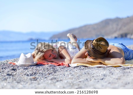 Young couple is lying on the beach and looking eachother