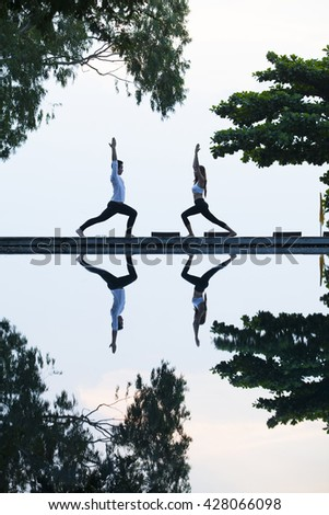 Young couple is practicing yoga at swimming pool by sky as background.