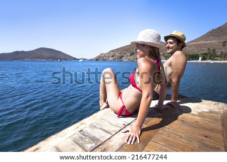 Young couple is sitting and sunbathing on a wooden port