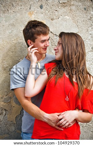 Young couple is standing grunge wall and hugging - stock photo