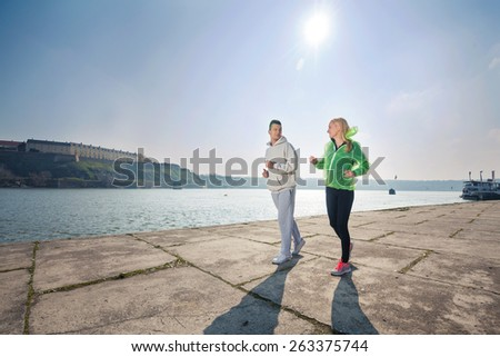 Young couple jogging by the river on a nice sunny day - stock photo