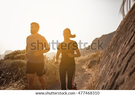 Young couple jogging down a mountain in full sun looking ahead of them while wearing running clothes