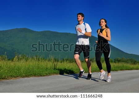 Young couple jogging in park at morning. Health and fitness. - stock photo