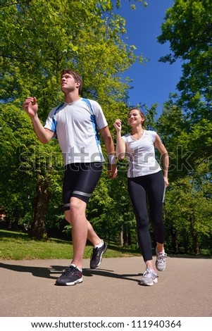 Young couple jogging in park at morning. Health and fitness concept
