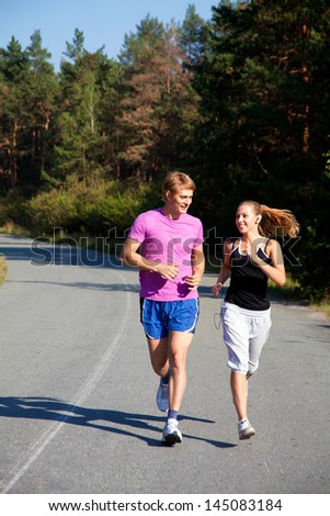 Young couple jogging on a morning park - stock photo