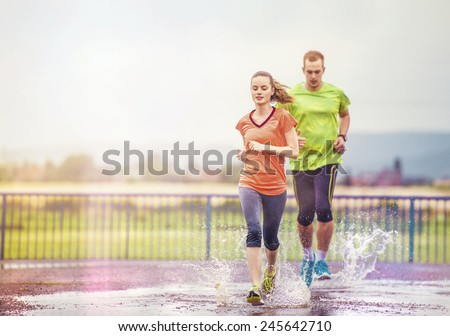 Young couple jogging on asphalt in rainy weather - stock photo