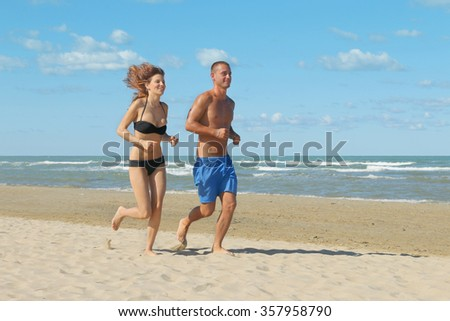 young couple jogging on beach doing fitness on holiday - attractive girl and boy running on the seashore on a sunny day