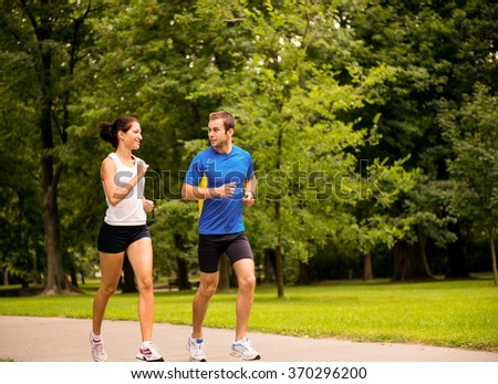 Young couple jogging outdoor and looking on each other - stock photo