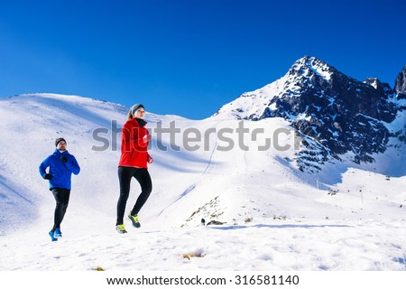 Young couple jogging outside in sunny winter mountains - stock photo